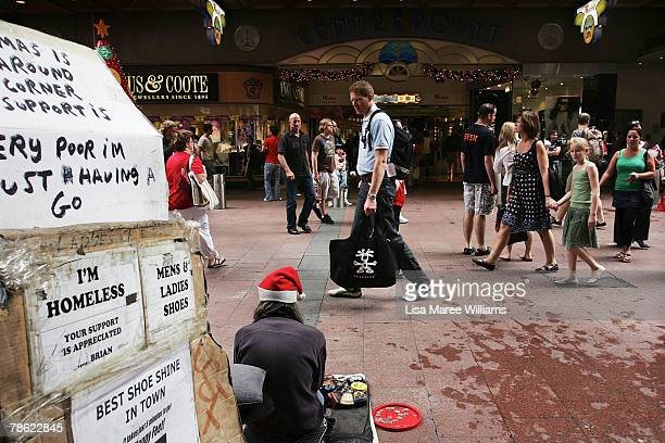 A homeless man sits in Pitt Street Mall as Christmas shoppers pass by on December 22 2007 in Sydney Australia Sydney residents are preparing for...
