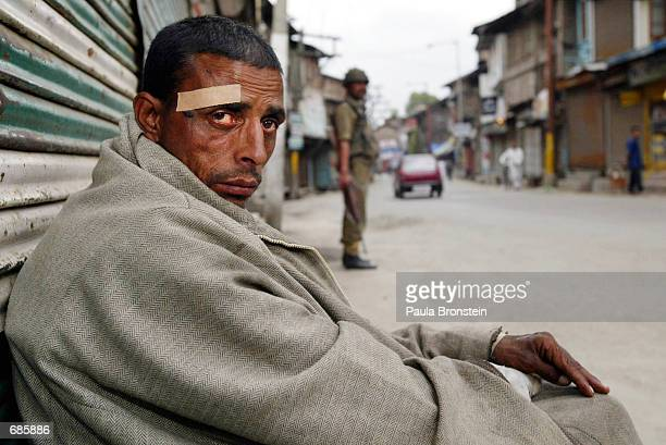 A homeless man sits on a curb June 11 2002 in Srinagar the summer capital of the Indian held state of Kashmir A strike organized by the proPakistani...