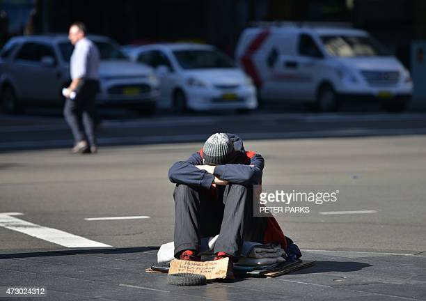 A homeless man sits on a street in the Central Business District of Sydney as the Australian government prepares to release its 2015/16 budget on May...