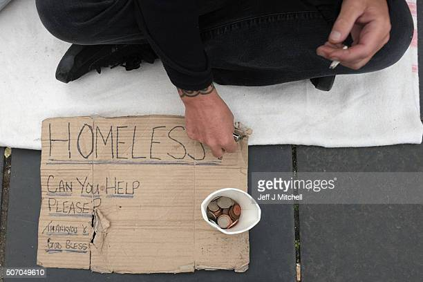 A homeless man sits on Princess Street on August 24 2015 in Edinburgh Scotland Thousands of households in the UK are slipping below the poverty line...