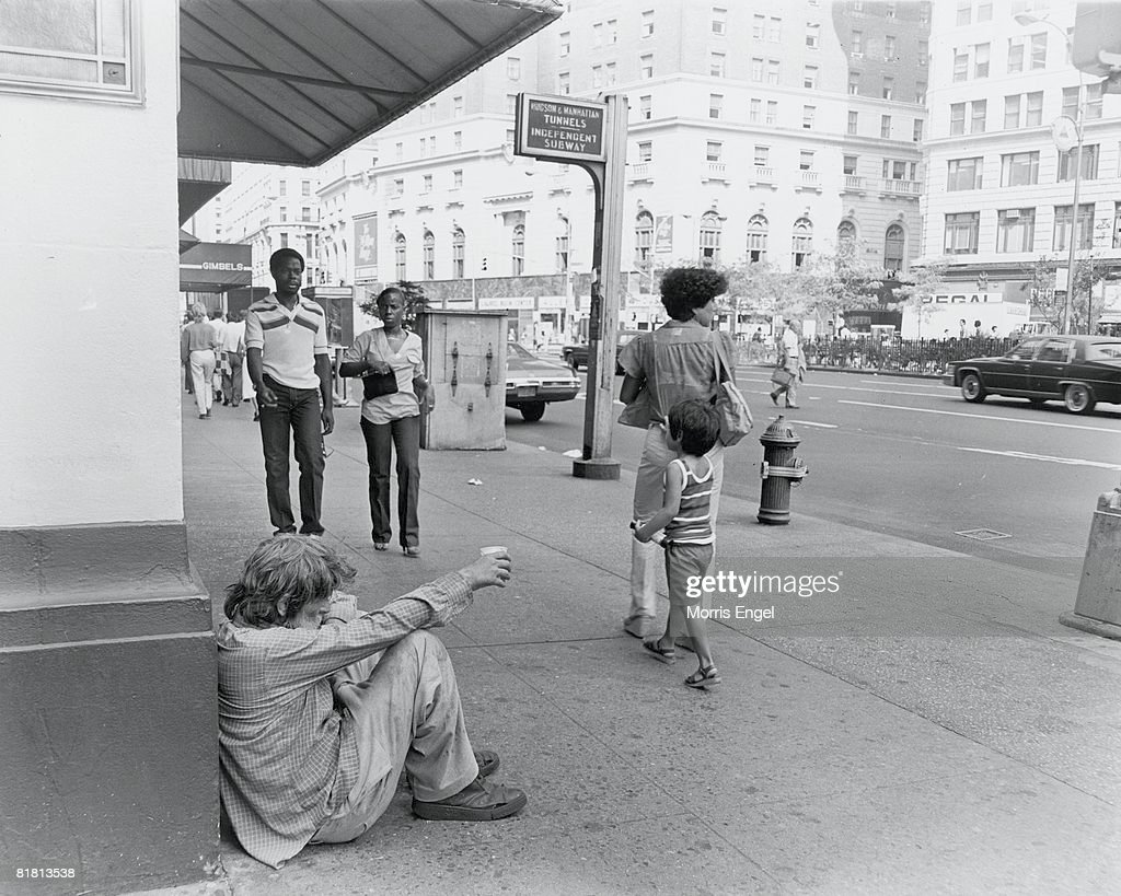 A homeless man sits on the sidewalk in front of Gimbels department store, a paper cup in his outstretched hand, New York, New York, early 1980s. The store, which closed in 1986, was located on 6th Ave between West 33rd and West 32nd streets.