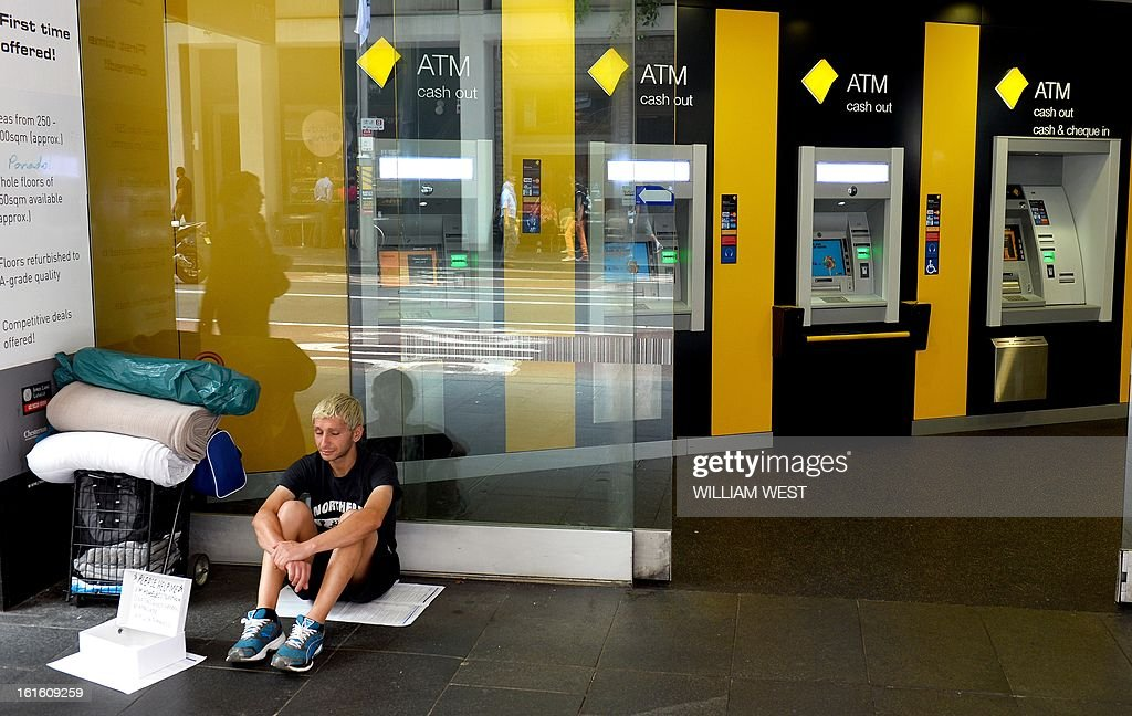 A homeless man sits outside an inner-city branch of Australia's largest lender Commonwealth Bank which posted a one percent rise in first-half net profit to Aus$3.66 billion (US$3.77 billion) despite subdued market conditions, in Sydney on February 13, 2013. The bank's result for the six months to December 31 was up from $3.62 billion in the same period the previous year. Its cash profit, a measure often preferred by financial institutions, rose six percent to Aus$3,78 billion, slightly above analyst expectaions. AFP PHOTO/William WEST