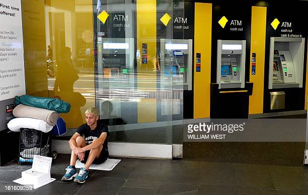 A homeless man sits outside an innercity branch of Australia's largest lender Commonwealth Bank which posted a one percent rise in firsthalf net...