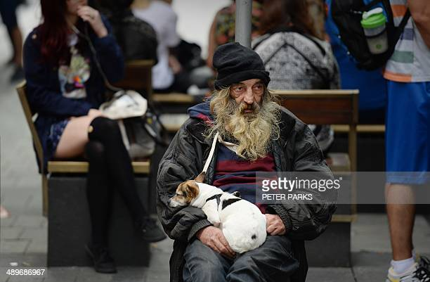 A homeless man sits with his dog on a street in Sydney on May 12 2014 Australia's first budget under conservative Prime Minister Tony Abbott to be...