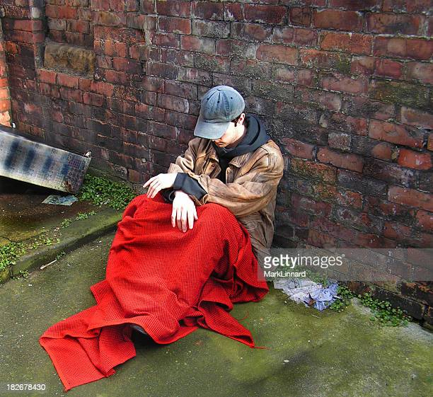 Homeless man sitting by a brick wall under a red blanket