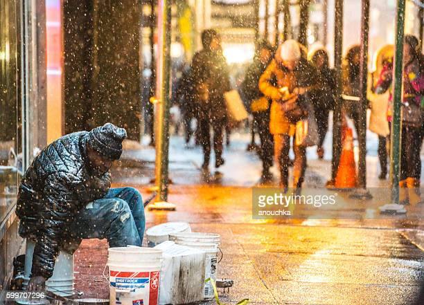 Homeless man sitting on New York street under snow