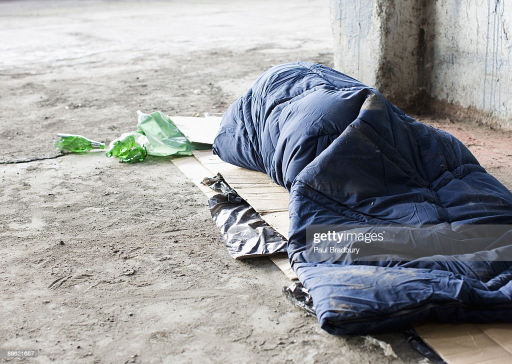 Homeless man sleeping in sleeping bag on cardboard : Stock Photo