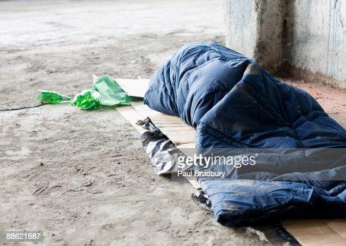 Homeless hombre durmiendo en saco de dormir en cartón : Foto de stock