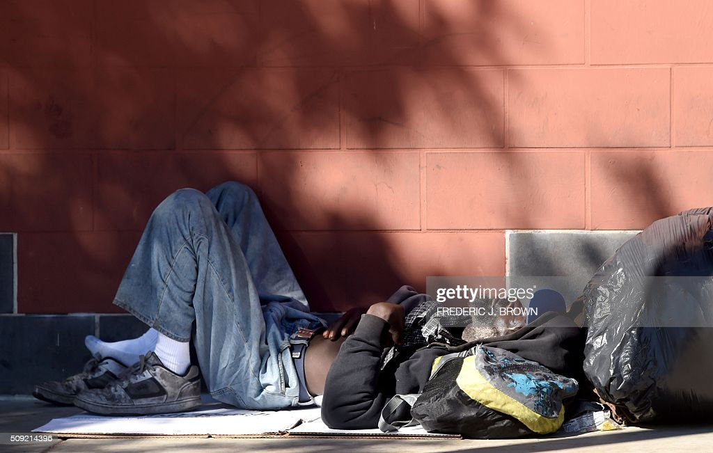 A homeless man sleeps beside the wall on the sidewalk along a street in downtown Los Angeles, California on February 9, 2016. Los Angeles City and County officials are voting February 9 on plans aimed at ending homelessness in the community, mostly by making permanent housing available to the tens of thousands of people who are homeless. / AFP / Frederic J. BROWN