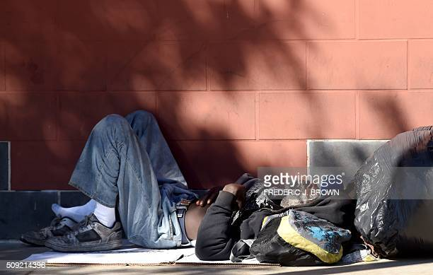 A homeless man sleeps beside the wall on the sidewalk along a street in downtown Los Angeles California on February 9 2016 Los Angeles City and...