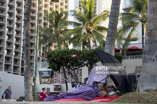 A homeless man sleeps by Waikiki beach in Honolulu on December 20 2014 According to the 2014 State of Homelessness in America report Hawaii ranks...