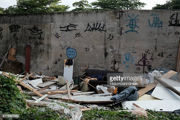 A homeless man sleeps in a couch in the open amid the debris of his shack on April 30 2015 early morning in Rio de Janeiro Brazil Some 40 shacks...