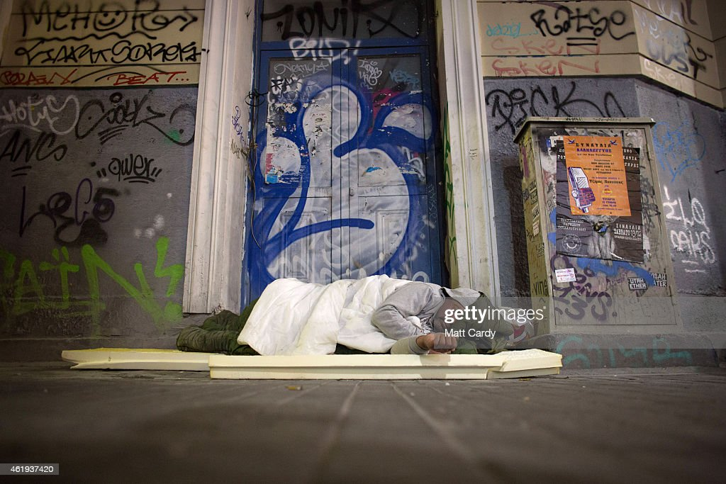 A homeless man sleeps in a doorway on the streets of Athens ahead of this weekend general election on January 21 2015 in Athens Greece According to...