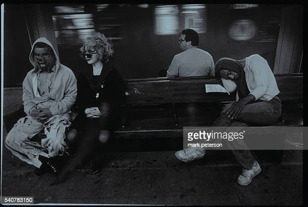 A homeless man sleeps next to two people wearing costumes while waiting for the subway
