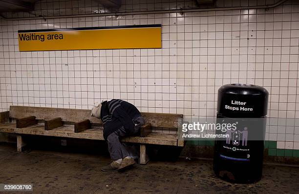 A homeless man sleeps on a bench in the subway