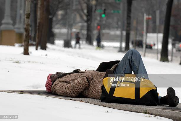A homeless man sleeps on a grate on North Capitol Street