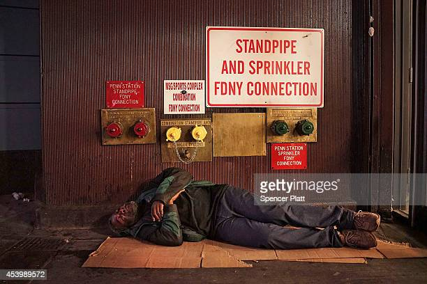 A homeless man sleeps on a Manhattan street on August 22 2014 in New York City According to the Department of Homeless Services the number of...