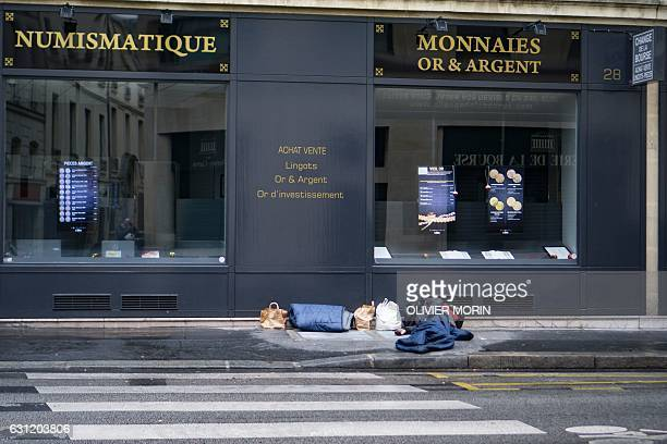 A homeless man sleeps on a street in central Paris on January 8 as a cold wave hits much of Europe / AFP / OLIVIER MORIN