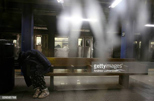 A homeless man sleeps on a subway platform bench in New York City
