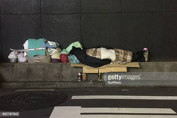 A homeless man sleeps on the pavement in front of a clothing store in Tokyo January 26 2017 Gas usage hits record highs in Tokyo Osaka as cold bites...
