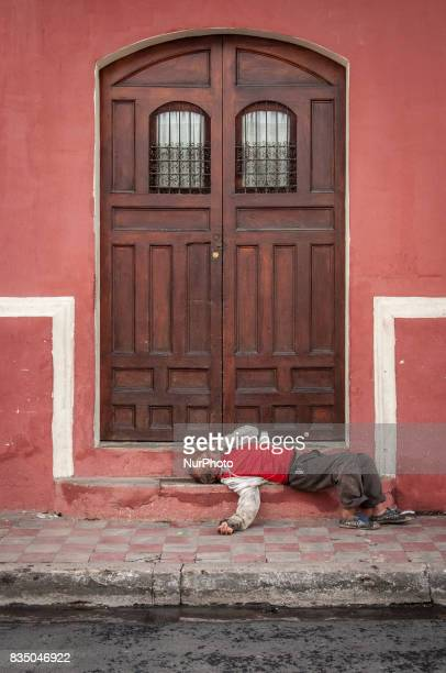 A homeless man sleeps on the step of a colonial home in Granada Nicaragua on 25 October 2011