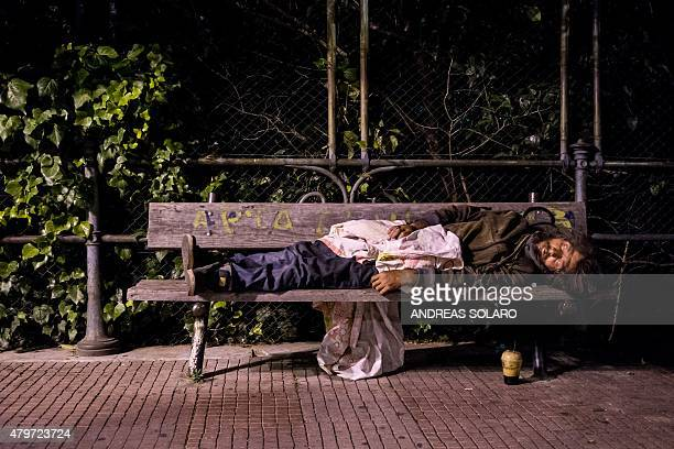 A homeless man sleeps onto a bench in downtown Athens on July 6 2015 Greeks declared in a referendum that they 'deserve better' and 'cannot accept a...