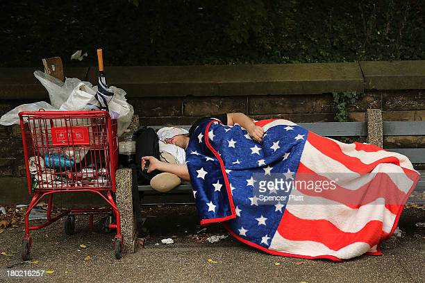 A homeless man sleeps under an American Flag blanket on a park bench on September 10 2013 in the Brooklyn borough of New York City As of June 2013...