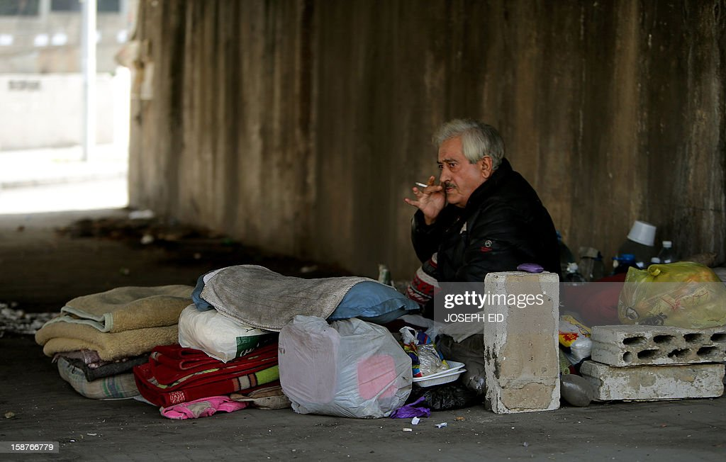 A homeless man smokes a cigarette as he sits on his mattress under a bridge in Beirut on December 28, 2012.
