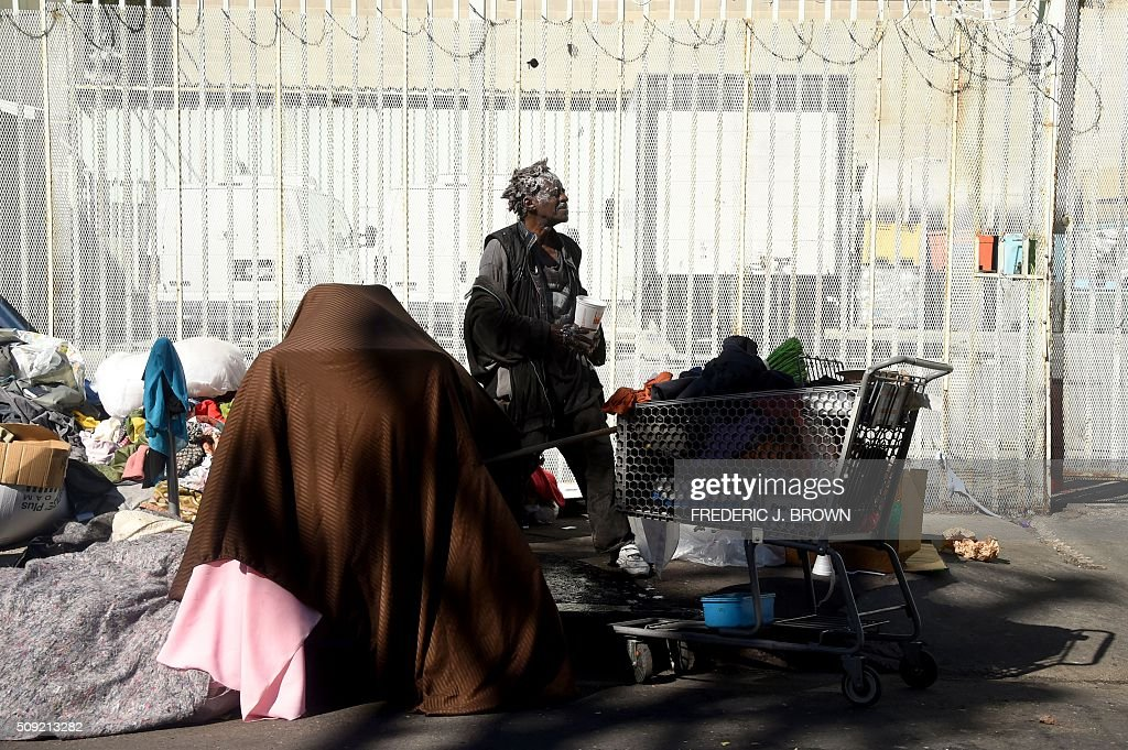 A homeless man stands amid his belongings on the street in Los Angeles, California on February 9, 2016. Los Angeles City and County officials are voting February 9 on plans aimed at ending homelessness in the community, mostly by making permanent housing available to the tens of thousands of people who are homeless. / AFP / Frederic J. BROWN