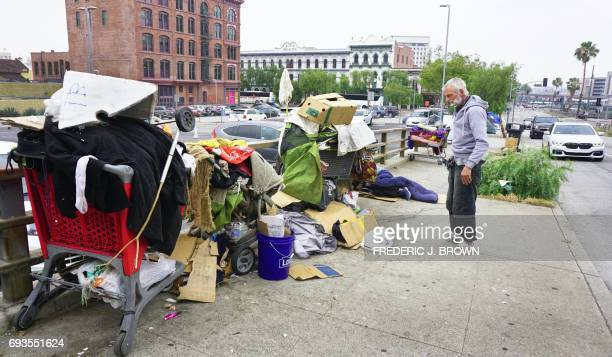A homeless man stands before his belongings at his encampment on a downtown sidewalk as vehicles pass by in Los Angeles California on June 7 a city...