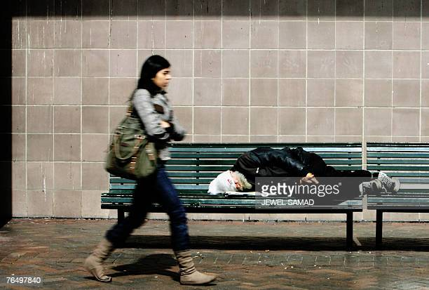 A homeless man takes a nap on a bench as a woman walks past along a street in Sydney 04 September 2007 as the city hosts the AsiaPacific Economic...
