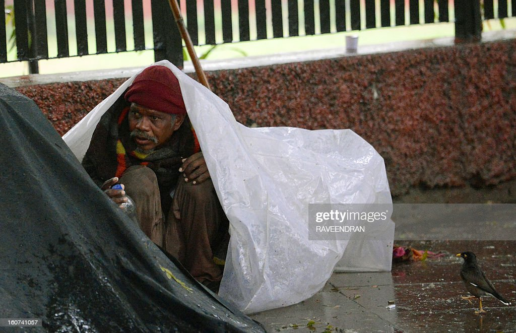 A homeless man takes shelter under a tarp as rain falls in New Delhi on February 5, 2013. Heavy rains lashed the Indian capital bringing down the mercury and throwing normal life out of gear. AFP PHOTO/RAVEENDRAN