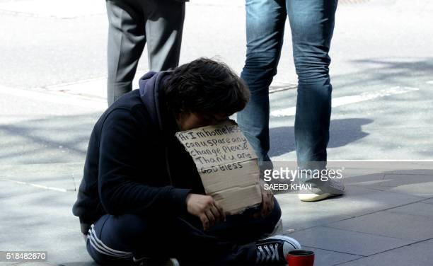 A homeless man waits for charity in the central business district of Sydney on April 2016 The Australian economy has slowed as the country exits an...