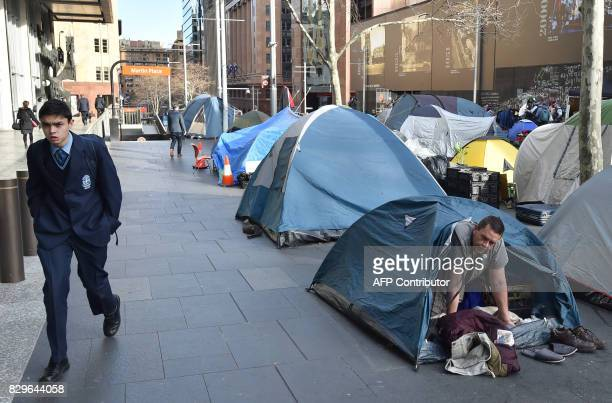 A homeless man wakes up in his tent in Martin Place which has become known as 'Tent City' in the central business district of Sydney on August 11...