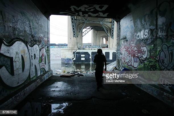 A homeless man who goes by the name 'Pepper' walks through a tunnel at the place where he sleeps along the graffiticovered walls that line the banks...