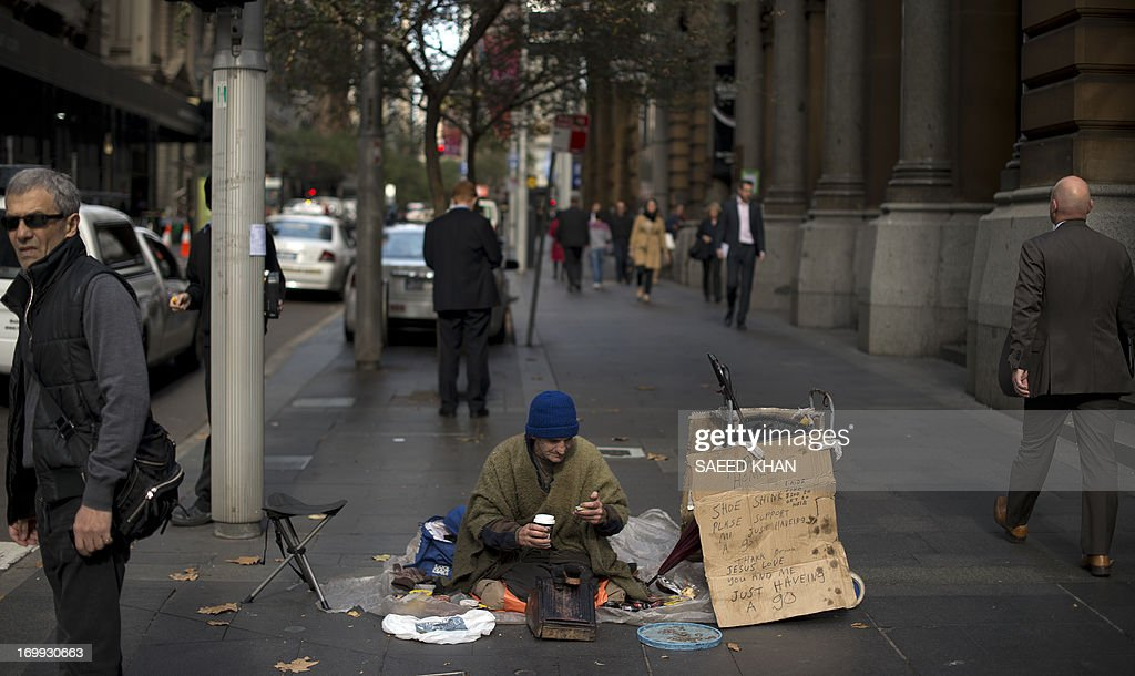 A homeless man who polishes shoes for a living sits in the middle of a walkway as he waits for customers in the central business district of Sydney on June 5, 2013. Homelessness in Australia has surged 17 percent since 2006 mainly due to a spike in migrant numbers, though fewer people are sleeping rough on the streets, a report found. The National Affordable Housing Agreement report, prepared by the government's COAG Reform Council, found that overall housing security had declined from 2006 to 2011. AFP PHOTO / Saeed KHAN