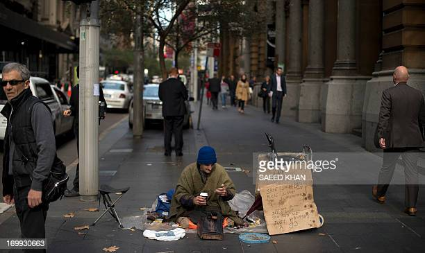 A homeless man who polishes shoes for a living sits in the middle of a walkway as he waits for customers in the central business district of Sydney...