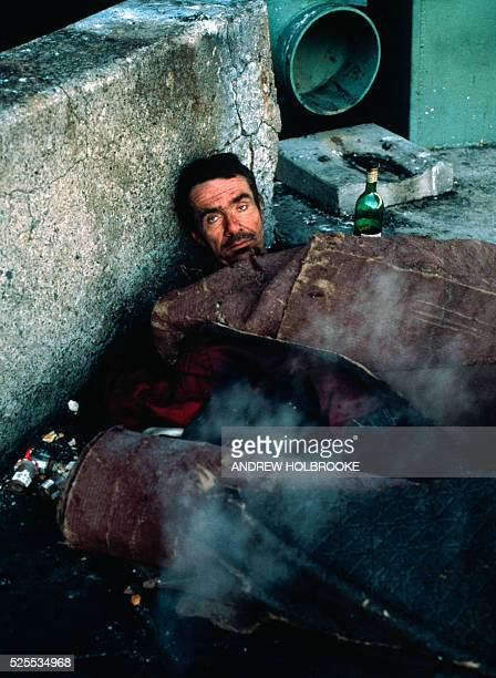 A homeless man with his bottle of wine by his side keeps warm by lying on top of a steam vent in the freezing winter temperatures
