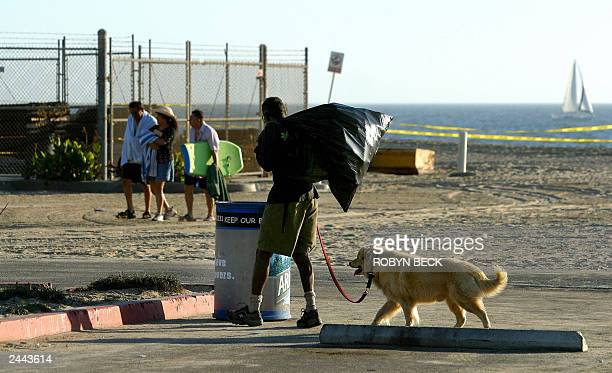 A homeless man with his dog stops at a trash bin to search for recyclable cans as beachgoers head home for the day at Venice Beach in Los Angeles...