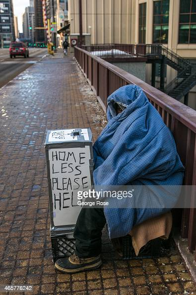 A homeless man wrapped in blankets begs for money on a deserted bridge in subzero weather on March 2 2015 in Chicago Illinois Some of the coldest...