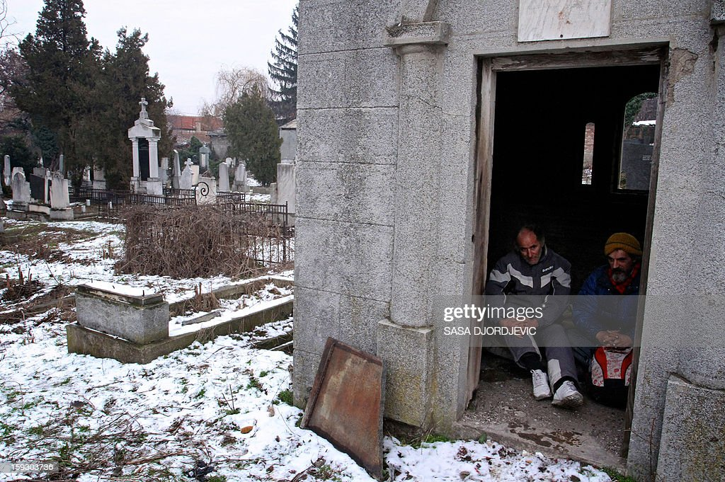 Homeless men Bratislav Jovanovic (R), 43, and Aleksandar Dejic, 50, sit on January 10, 2013 inside a tomb at a cemetery in Nis, 200 kilometres south of Belgrade. Both men have been homeless for nearly twenty years since they lost their family members. The last 15 years they've live in tombs and graves beside the caskets of their decedents. During winter time with outside temperatures dropping below zero they take shelter in the graves or above ground tombs at the old cemetery.