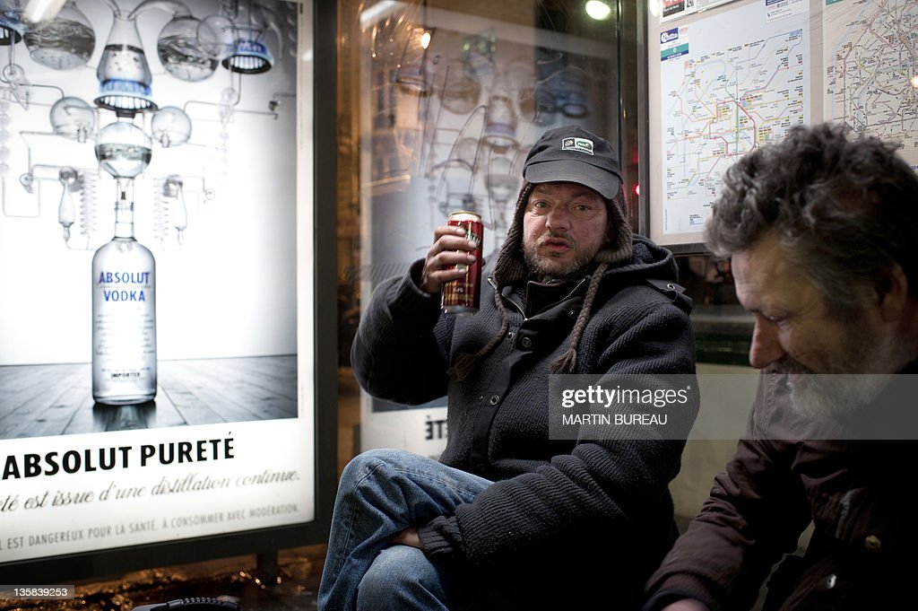 Homeless men drink a beer at a bus shelter during an assistance operation of the Order of Malta assocation on December 14 2011 in Paris AFP PHOTO /...