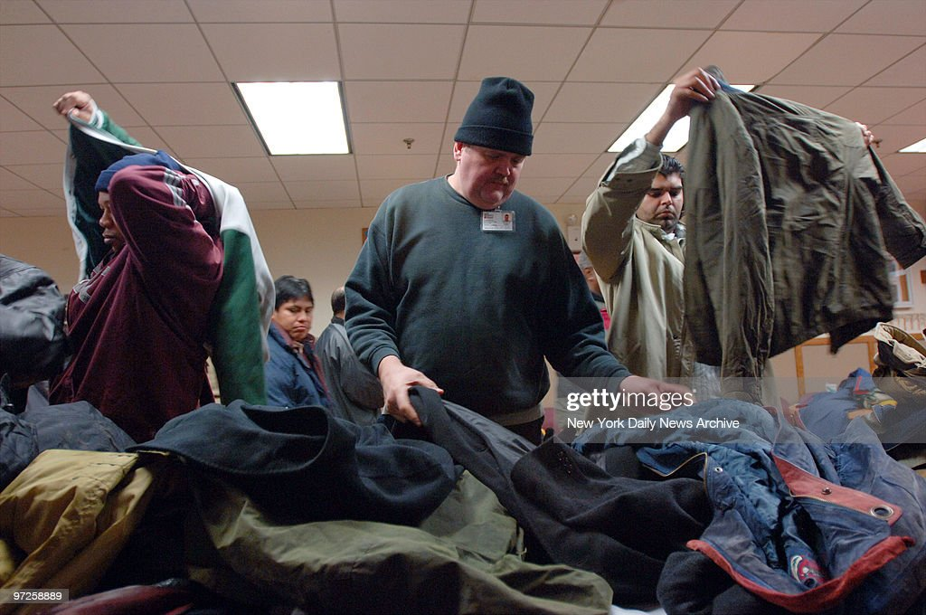 Homeless men look through a pile of donated coats during the 18th annual New York Cares coat drive at the Bowery Mission