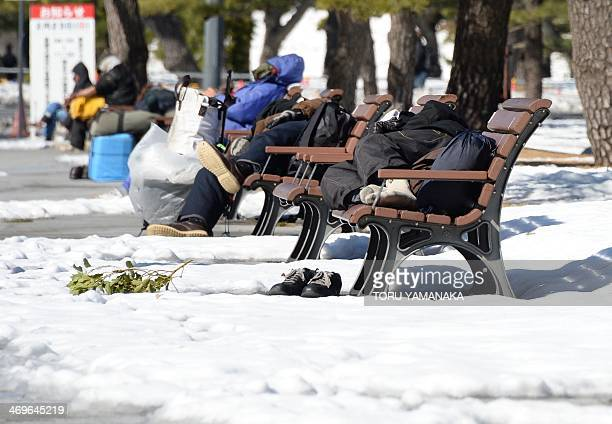 Homeless men take naps on benches at a park in Tokyo on February 16 2014 after a snow storm hit Japan Two people were killed when a fresh snow storm...