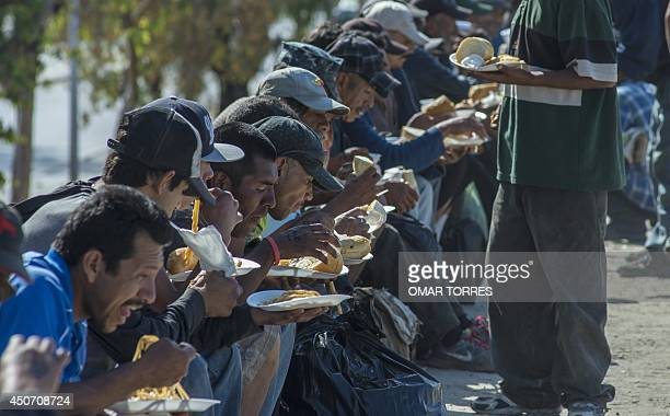 Homeless most of them deported from the United States eat a lunch brought by a local church at the canal of the Tijuana river in Tijuana City Mexico...