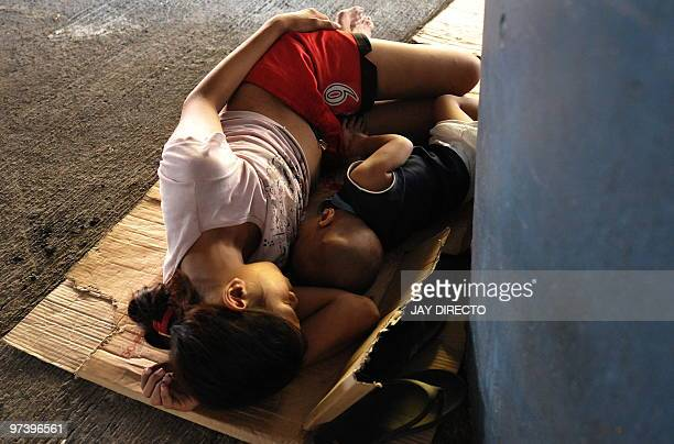 A homeless mother and child sleep on a side walk in Manila on March 3 2010 Outgoing Philippines President Gloria Arroyo defended her economic...