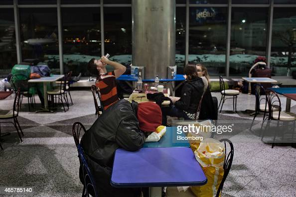 A homeless New Yorker sleeps while stranded travelers wait for flights in the food court atrium in Terminal B of LaGuardia Airport in New York on...