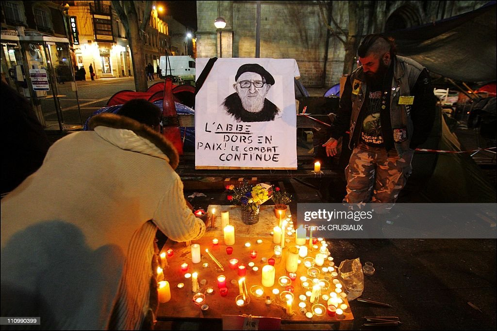 "Homeless of the Lille camp of ""the Children of Don Quixote 'and passers make a final tribute to Abbe Pierre by collecte or submitte a candle at the foot of his portrait in Lille, France on January 25th, 2007"