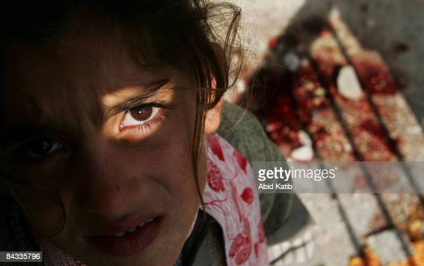 A homeless Palestinian girl stands beside a patch of blood at a United Nations school after it was hit by Israeli shelling on January 17 2009 in Beit...