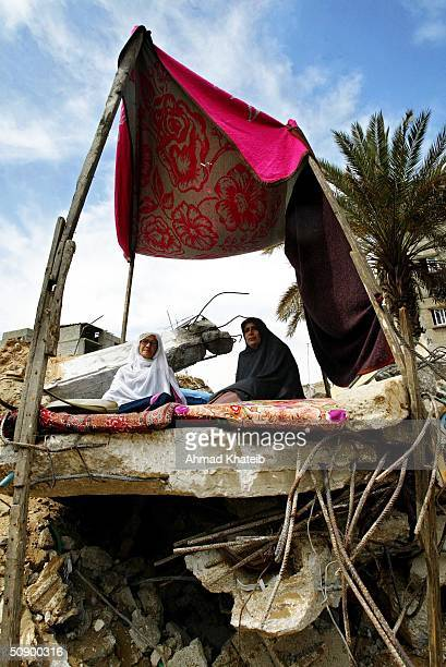 Homeless Palestinian women sit in a makeshift tent on the rubble of their home which was destroyed by the Israeli Army in a recent raid May 26 2004...